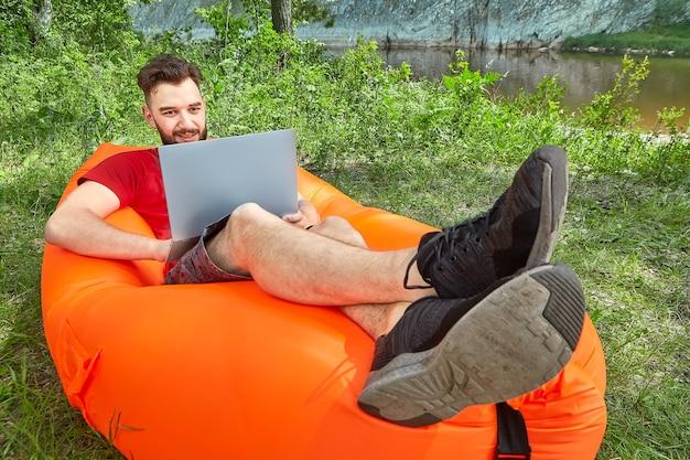 Il giovane uomo d'affari barbuto con il taccuino è rilassante sul lettino gonfiabile arancione durante l'ecoturismo vicino al fiume.