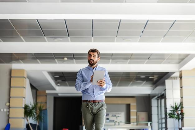 Giovane ceo barbuto che cammina nella hall della sua azienda e utilizza il tablet per controllare come stanno andando gli affari.