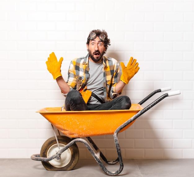 Giovane barbuto operaio edile uomo su una carriola