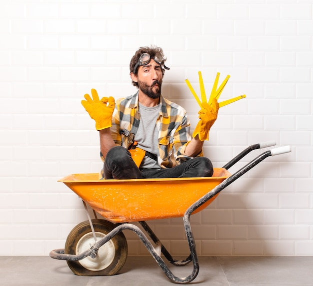 Giovane operaio edile barbuto su una carriola