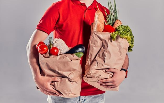 Un giovane corriere barbuto con una maglietta rossa e un berretto tiene in mano due pesanti sacchi di cibo. cibo a domicilio.