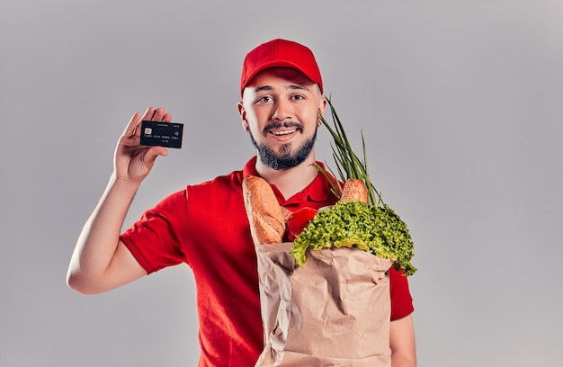 Un giovane corriere barbuto con una maglietta rossa e un berretto con un pacco di cibo tiene in mano una carta di credito, offrendo pagamento non in contanti. cibo a domicilio.