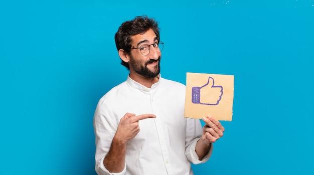 Giovane uomo pazzo barbuto che tiene un social media come foglio