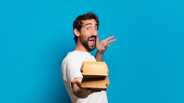Giovane uomo pazzo barbuto che tiene un hamburger da asporto