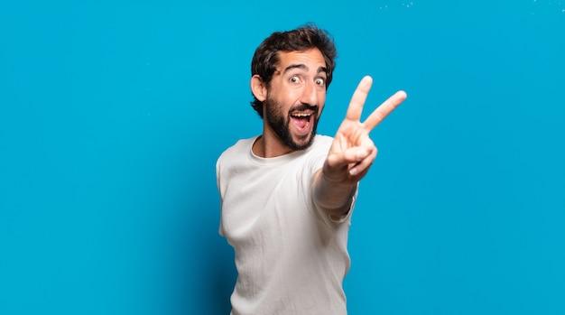 Giovane uomo pazzo barbuto che mostra due dita
