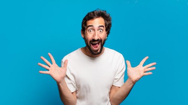 Giovane uomo pazzo barbuto sorpreso con uno spazio di copia