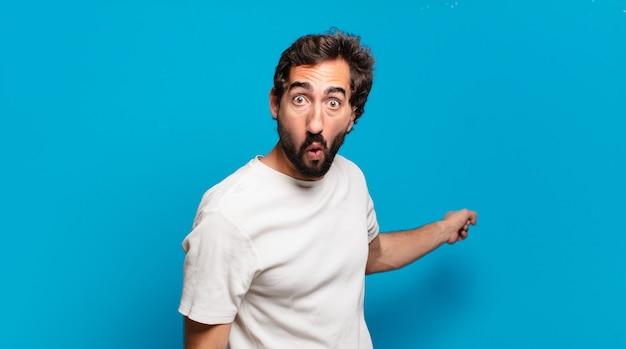 Giovane pazzo barbuto con uno spazio di copia. espressione scioccata