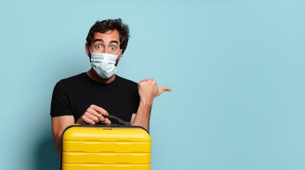 Giovane barbuto pazzo con una maschera protettiva covid. concetto di viaggio