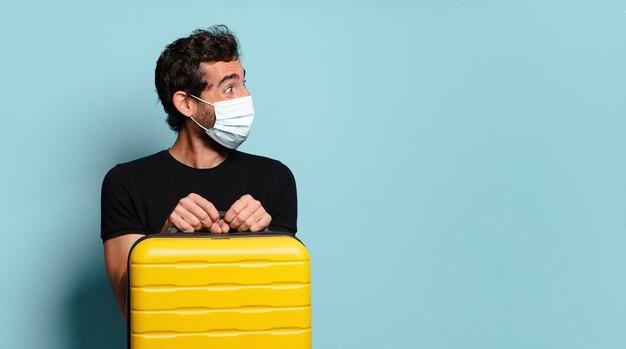 Giovane pazzo barbuto con una mascherina di protezione covid. concetto di viaggio