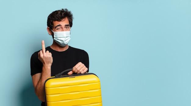 Giovane pazzo barbuto con una maschera protettiva covid. concetto di viaggio