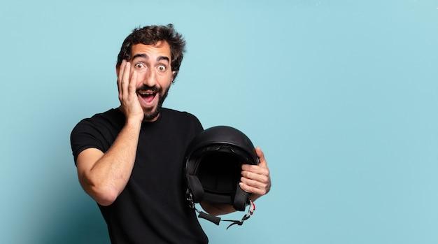 Giovane uomo pazzo barbuto con un casco da motocicletta