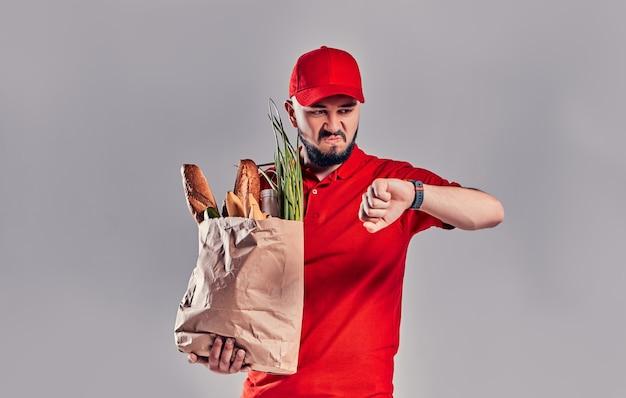 Il giovane fattorino barbuto arrabbiato dispiaciuto in uniforme rossa tiene un pacchetto con pane e verdure e guarda lo smartwatch sulla sua mano che è in ritardo isolato su sfondo grigio.