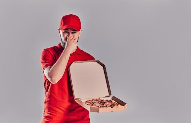 Giovane fattorino barbuto in uniforme rossa con pizza si copre il naso con la mano da un odore sgradevole isolato su sfondo grigio.