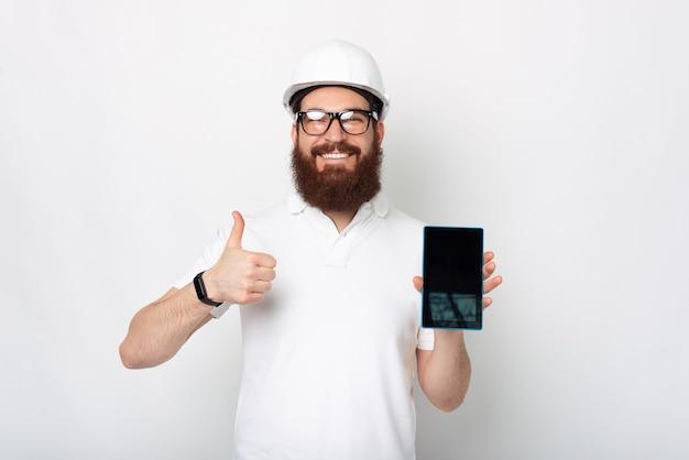 Il giovane ingegnere barbuto sta tenendo un tablet e mostrando il pollice in su.