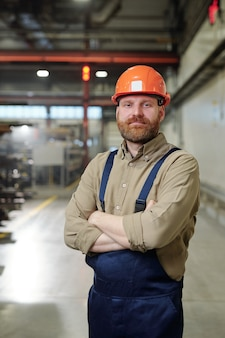Giovane ingegnere barbuto con le braccia incrociate in piedi nel suo posto di lavoro all'interno dell'impianto industriale