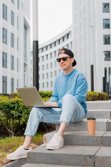 Giovane uomo d'affari barbuto hipster si trova sulla strada della città con una tazza di caffè e utilizza computer tablet. moderno edificio in vetro uomo che lavora blogging in chat online sui social media