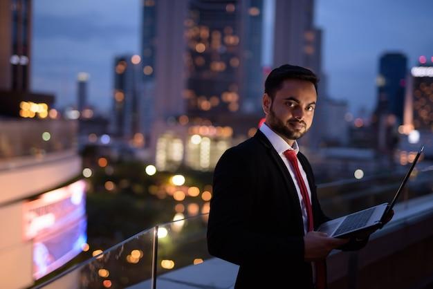 Giovane imprenditore indiano barbuto contro la vista della città di notte