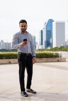 Giovane imprenditore indiano barbuto rilassante presso il parco