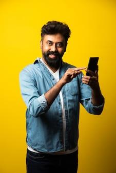 Giovane indiano barbuto che usa lo smartphone, sorride mentre chiama o chiacchiera con un amico, in piedi sul giallo