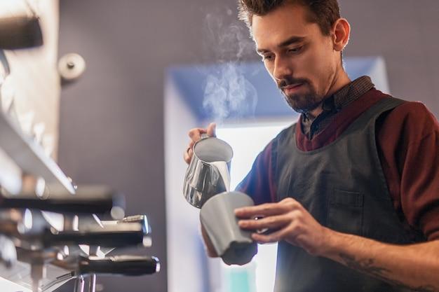 Giovane barista maschio barbuto versando il latte nella tazza di caffè