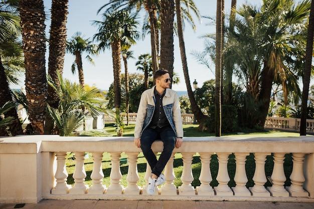 Il giovane maschio barbuto in uno streetwear è seduto sulle recinzioni e si rilassa nella zona urbana vicino alle palme.