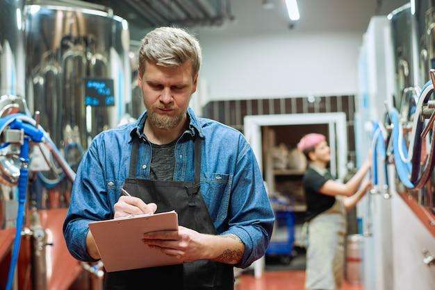 Giovane lavoratore maschio barbuto della fabbrica di produzione di birra che prende appunti mentre si trova contro la birraia che lavora con una grande macchina di lavorazione