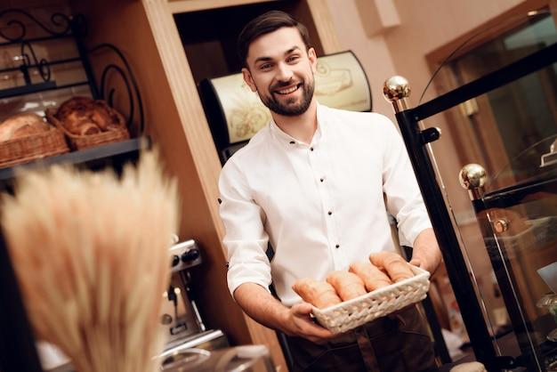Giovane uomo barbuto in grembiule che sta nel forno.