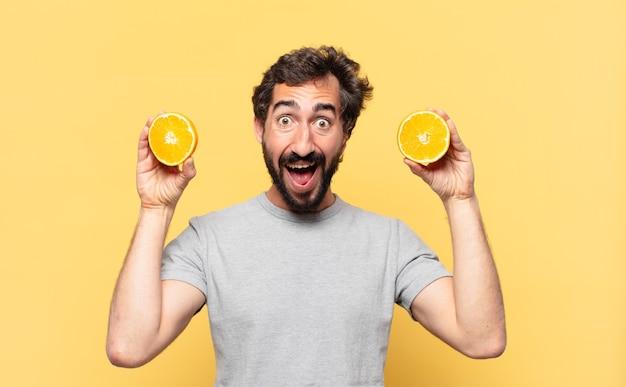 Giovane uomo barbuto a dieta espressione sorpresa e con in mano un'arancia