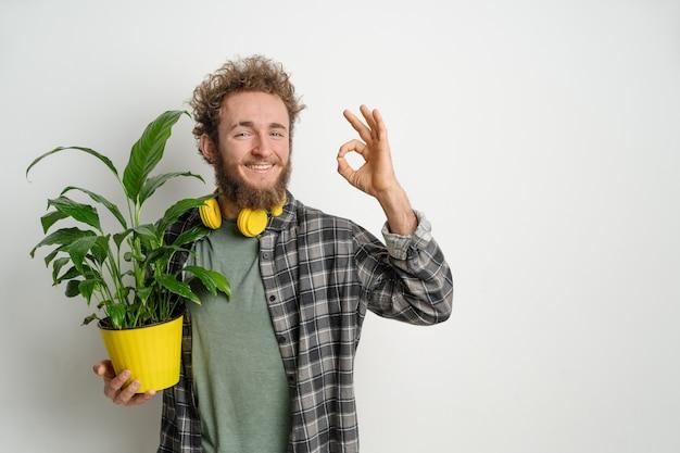 Giovane uomo barbuto, vestito con una camicia a quadri, che tiene un vaso di fiori giallo con la pianta e che mostra il gesto giusto isolato sul muro bianco