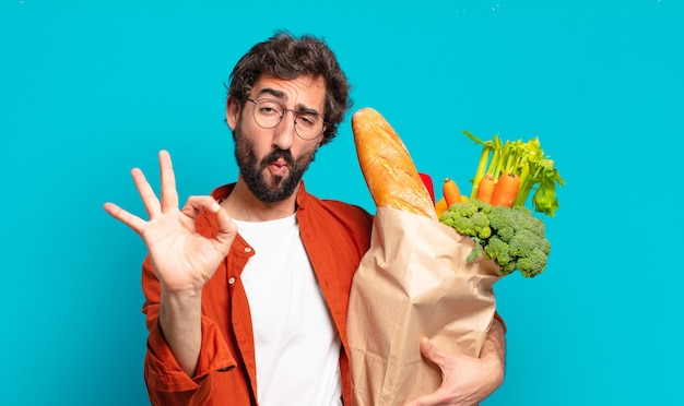 Giovane uomo barbuto che si sente felice, rilassato e soddisfatto, mostrando approvazione con un gesto ok, sorridendo e tenendo in mano un sacchetto di verdure