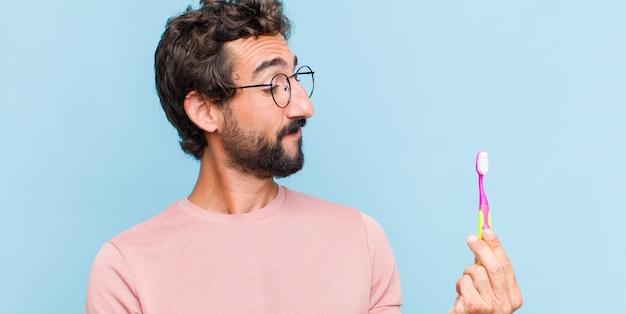 Giovane uomo barbuto che si sente felice e sorridente casualmente, guardando un oggetto o un concetto tenuto sulla mano sul lato
