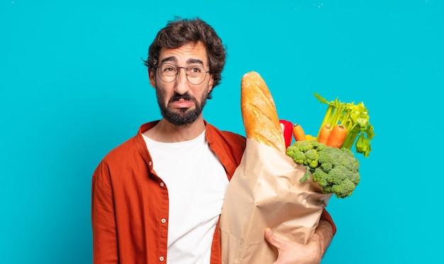 Giovane uomo barbuto che si sente triste e piagnucoloso con uno sguardo infelice, piange con un atteggiamento negativo e frustrato e tiene in mano un sacchetto di verdure