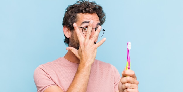 Giovane uomo barbuto che si sente spaventato o imbarazzato, sbirciando o spiando con gli occhi semicoperti dalle mani