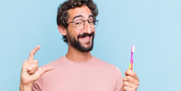 Giovane uomo barbuto che incornicia o delinea il proprio sorriso con entrambe le mani, guardando positivo e felice, concetto di benessere