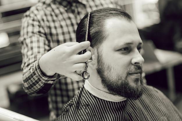 Giovane uomo barbuto che ottiene taglio di capelli mentre era seduto in poltrona al negozio di barbiere