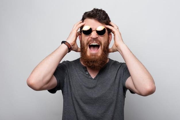 Giovane uomo barbuto che ha mal di testa, urla forte e si tiene le mani sulla testa.