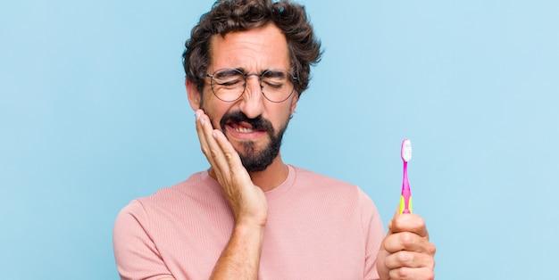 Giovane uomo barbuto che tiene la guancia e soffre di mal di denti doloroso, sensazione di malessere, miserabile e infelice, alla ricerca di un dentista