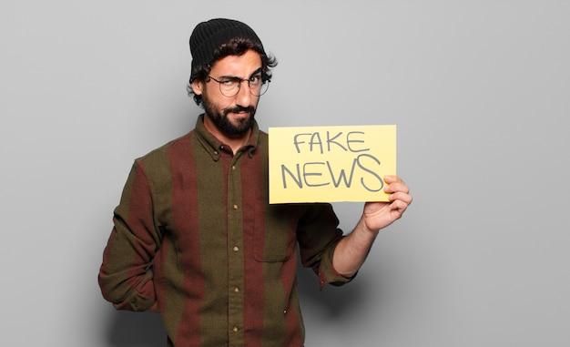 Giovane uomo barbuto che tiene scheda di notizie false