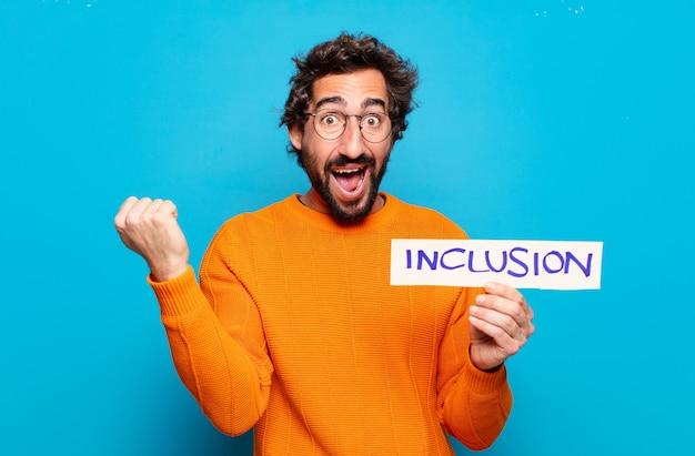 Giovane uomo barbuto che tiene un concetto di inclusione dell'insegna di inclusione
