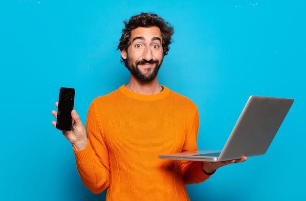 Giovane uomo barbuto che tiene un computer portatile. concetto di social media
