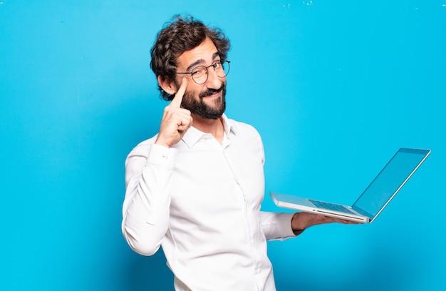 Giovane uomo barbuto che tiene un computer portatile
