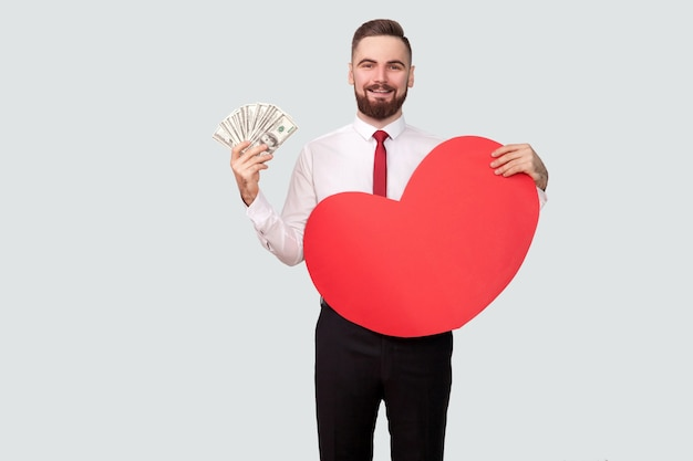 Giovane uomo barbuto che tiene molti dollari e forma di cuore rosso e guarda la telecamera con un sorriso a trentadue denti. al coperto, girato in studio, isolato su sfondo grigio