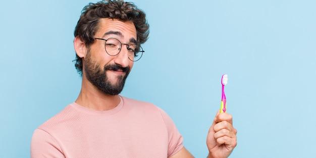 Giovane uomo barbuto che tiene un oggetto con entrambe le mani sullo spazio della copia laterale, mostrando, offrendo o pubblicizzando un oggetto