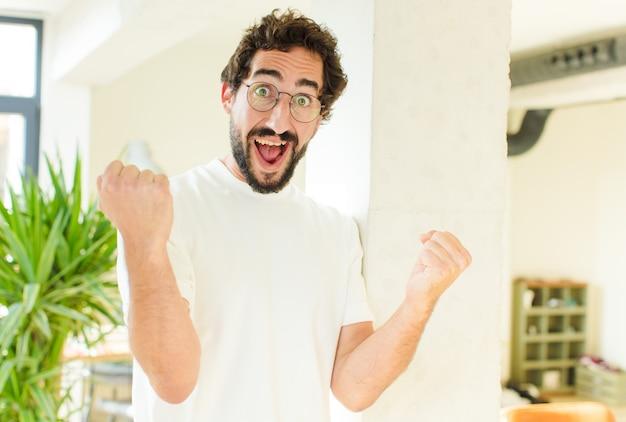 Giovane uomo barbuto a casa. espressione sorpresa
