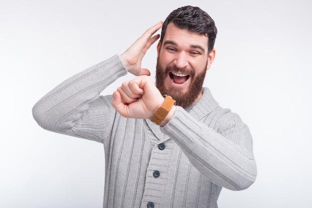 Il giovane uomo con la barba ha paura di essere in ritardo, sta guardando il suo orologio intelligente.