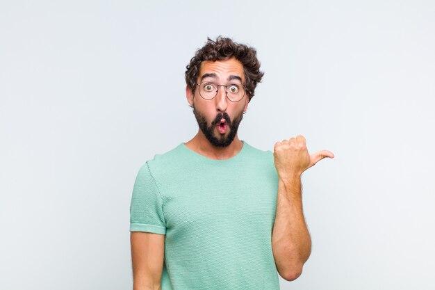 Giovane uomo barbuto che guarda stupito incredulo, indicando un oggetto sul lato e dicendo wow, incredibile