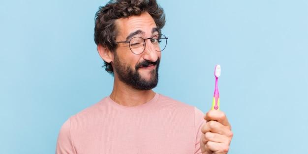 Giovane uomo barbuto che sembra felice e amichevole, sorridente e ammiccante con un atteggiamento positivo Foto Premium