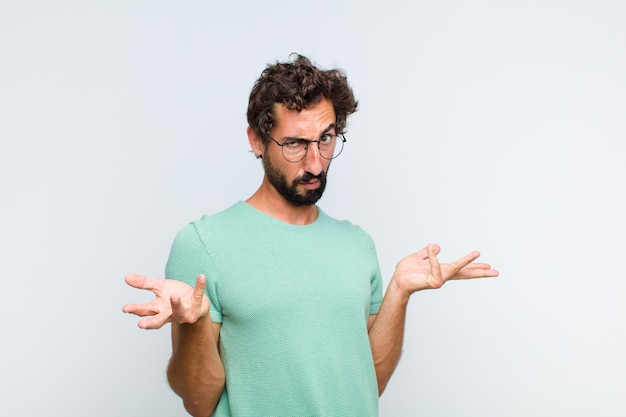 Giovane uomo barbuto che sembra perplesso, confuso e stressato, chiedendosi tra diverse opzioni, sentendosi incerto