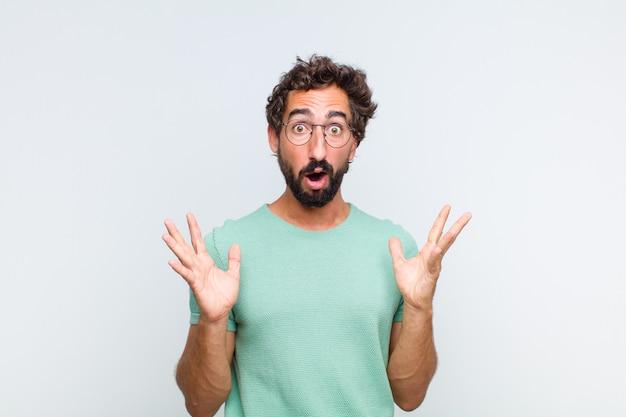 Giovane uomo con la barba che sembra scioccato e stupito, con la bocca aperta per la sorpresa quando realizza qualcosa di incredibile