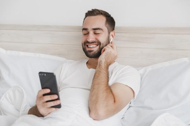Giovane uomo barbuto sdraiato a letto con coperta di cuscino lenzuolo bianco in camera da letto a casa